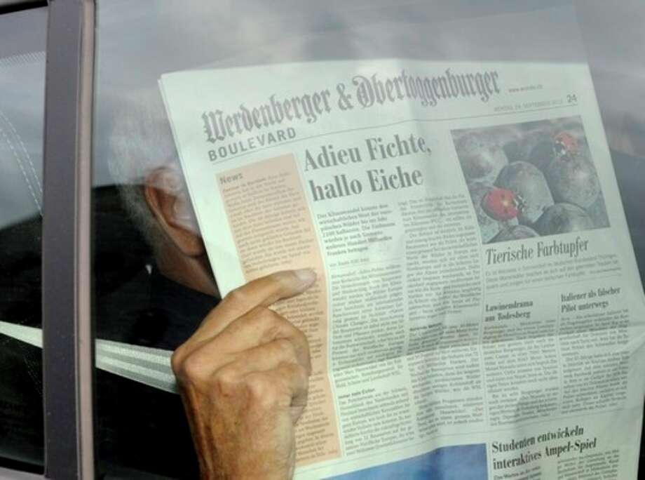 Swiss engineer Friedrich Tinner hides behind a newspaper as he leaves the Swiss Federal Criminal Court in Bellinzona, Switzerland, Tuesday, Sept. 25, 2012. The court has found him and his two sons guilty of helping an international nuclear smuggling ring that supplied material and know-how to rogue states such as Moammar Gadhafi's Libya. (AP Photo/Keystone, Karl Mathis) / KEYSTONE