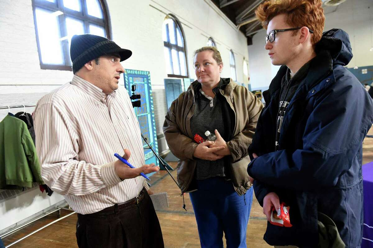 Dennis Yusko, left, of the Times Union interviews residents Heather Clifford, center, and her son Will Clifford, 16, about their village's water contamination on Saturday, Feb. 13, 2016, at HAYC3 Armory in Hoosick Falls, N.Y. The Cliffords had their blood drawn for PFOA testing through the state's Department of Health. (Cindy Schultz / Times Union)