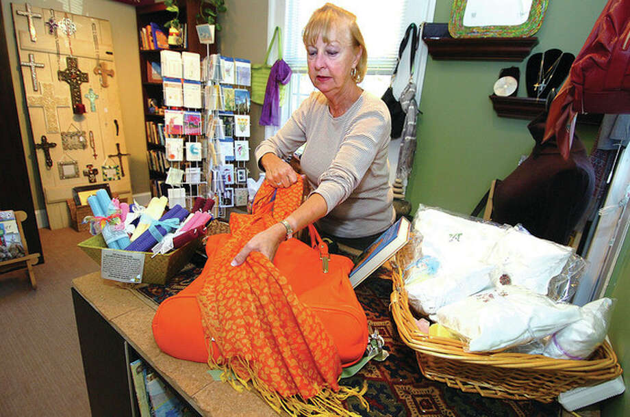 Hour Photo/ Alex von Kleydorff. Ginny Green , Manager/Buyer at St. Pauls Church, Standing Stones store straightens some purses and accesories for the display. / 2012 The Hour Newspapers
