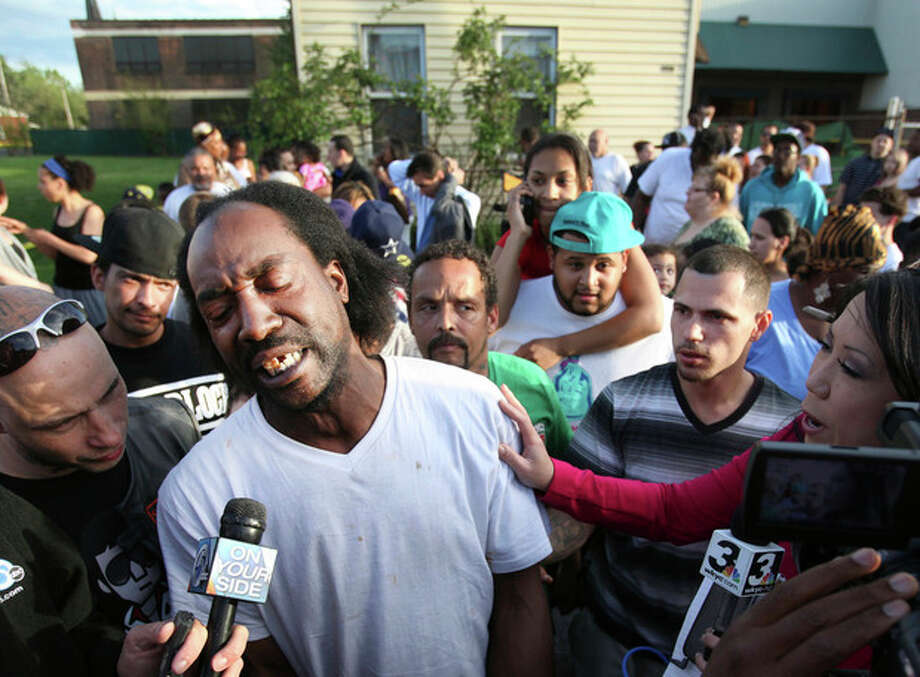 Neighbor Charles Ramsey speaks to media near the home on the 2200 block of Seymour Avenue, where three missing women were rescued in Cleveland, on Monday, May 6, 2013. Cheering crowds gathered on the street where police said Amanda Berry, Gina DeJesus and Michele Knight, who went missing about a decade ago and were found earlier in the day. (AP Photo/The Plain Dealer, Scott Shaw) MANDATORY CREDIT CLEVELAND PLAIN DEALER / The Plain Dealer