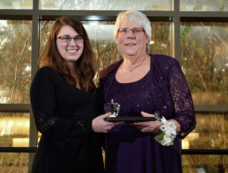 Mary Anne Forgach, right, was presented the Green Apple Teaching Award by former student Kayla Grotsky during a ceremony at Michigan State University in East Lansing. Grotsky graduated from MSU last month with a degree in computer science and credits Forgach for helping her go from failing math to advanced studies.
