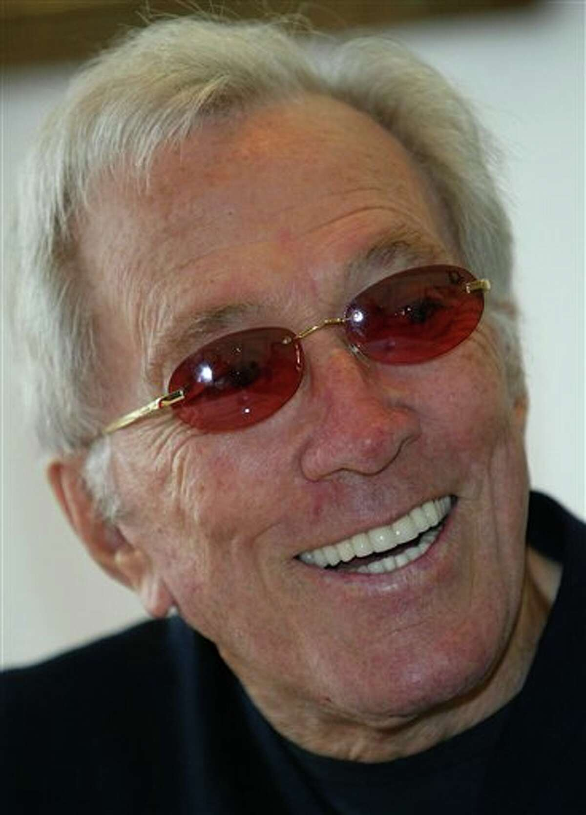 """FILE - In this July 25, 2004 file photo, U.S. singer Andy Williams smiles as he speaks to reporters during his news conference at a Tokyo hotel. Emmy-winning TV host and """"Moon River"""" crooner Williams died Tuesday night, Sept, 25, 2012 at his home in Branson, Mo., following a year-long battle with bladder cancer. He was 84. (AP Photo/Shizuo Kambayashi, File)"""