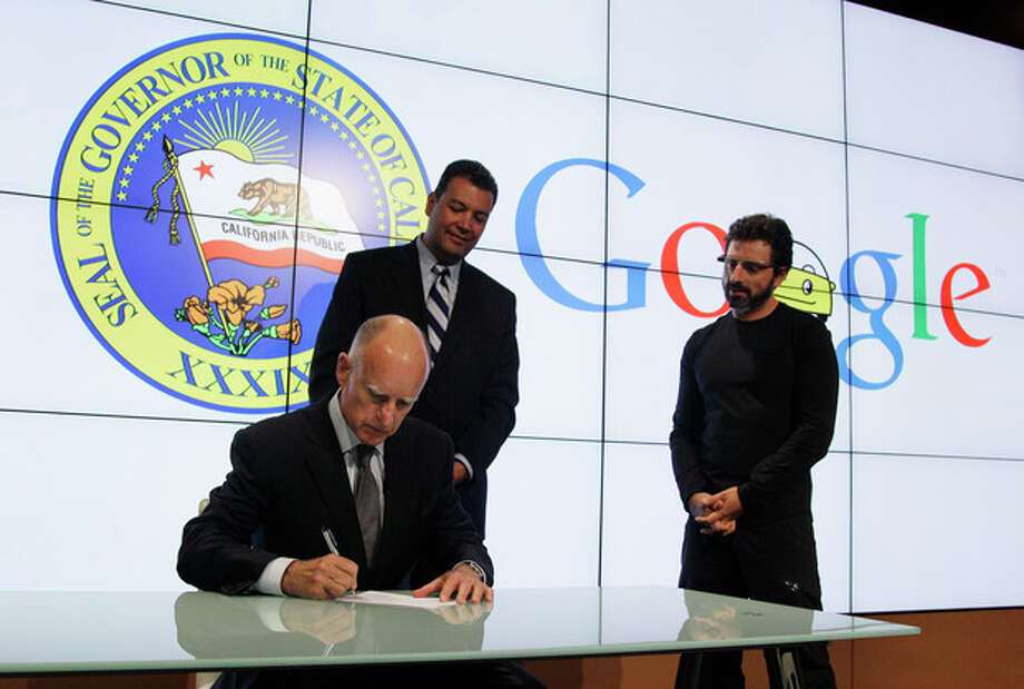 California Gov. Edmund G Brown Jr. signs a bill for driverless cars as state Senator Alex Padilla, center, and Google co-founder Sergey Brin, right, look on at Google headquarters in Mountain View, Calif., Tuesday, Sept. 25, 2012. The legislation will open the way for driverless cars in the state. Google, which has been developing autonomous car technology and lobbying for the legislation has a fleet of driverless cars that has logged more than 300,000 miles (482,780 kilometers) of self-driving on California roads. (AP Photo/Eric Risberg) / AP