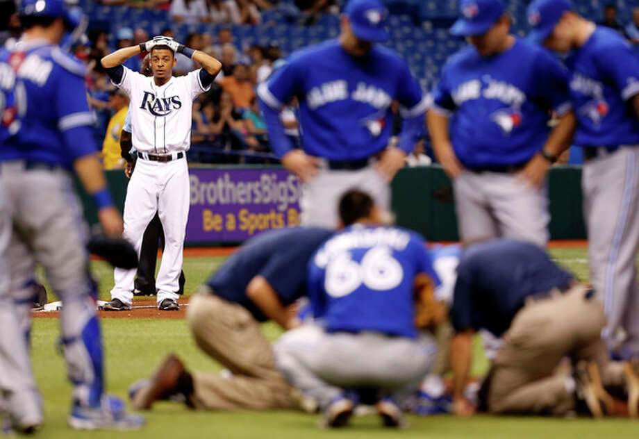 Tampa Bay Rays' Desmond Jennings reacts while medical personnel attend to Toronto Blue Jays starting pitcher J.A. Happ after during the second inning of a baseball game Tuesday, May 7, 2013, in St. Petersburg, Fla. Happ was hit by a line drive off of Jennings' bat. (AP Photo/Mike Carlson) / FR155492 AP
