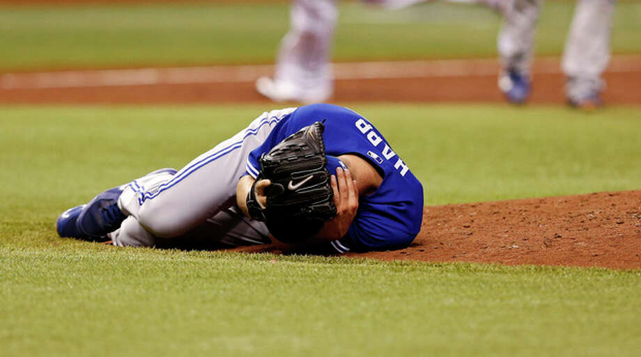 Toronto Blue Jays starting pitcher J.A. Happ reacts after being hit in the head with a line drive off the bat of Tampa Bay Rays' Desmond Jennings during the second inning of a baseball game Tuesday, May 7, 2013, in St. Petersburg, Fla. (AP Photo/Mike Carlson) / FR155492 AP