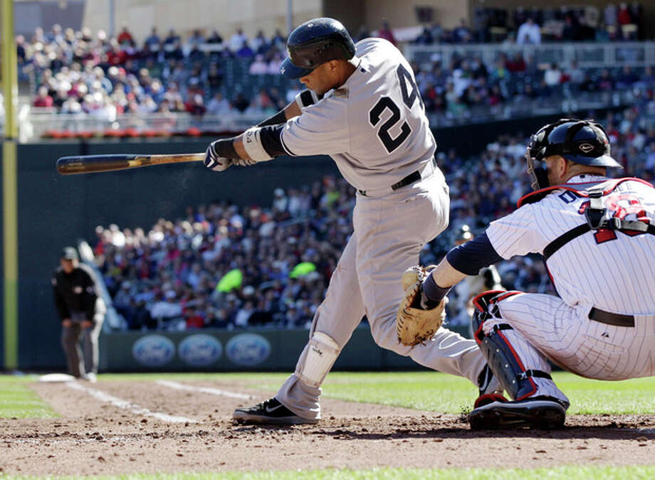 New York Yankees' Robinson Cano hits a two-run double in the third inning of a baseball game off Minnesota Twins pitcher Brian Duensing on Wednesday, Sept. 26, 2012 in Minneapolis. Catching is Twins' Ryan Doumit, right. (AP Photo/Jim Mone) / AP