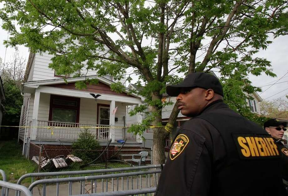 A sheriff deputy stands outside a house where three women escaped Tuesday, May 7, 2013, in Cleveland. Three women who went missing separately about a decade ago were found in the home Monday just south of downtown and likely had been tied up during years of captivity, said police, who arrested three brothers. (AP Photo/Tony Dejak) / AP