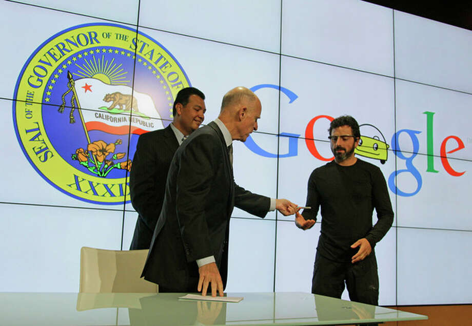 California Gov. Edmund G Brown Jr., center, hands his pen to Google co-founder Sergey Brin, right, after a bill signing for driverless cars at Google headquarters as state Senator Alex Padilla, left, looks on in Mountain View, Calif., Tuesday, Sept. 25, 2012. The legislation will open the way for driverless cars in the state. Google, which has been developing autonomous car technology and lobbying for the legislation has a fleet of driverless cars that has logged more than 300,000 miles (482,780 kilometers) of self-driving on California roads. (AP Photo/Eric Risberg) / AP