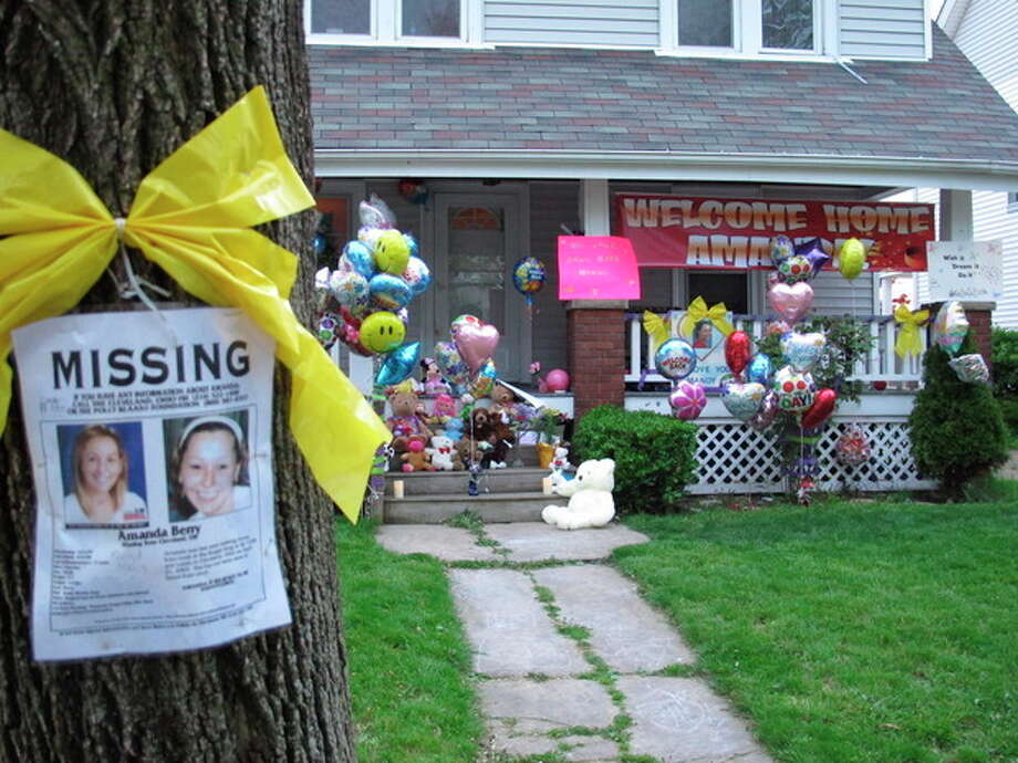 A collection of celebratory balloons and stuffed animals crowds the entrance to the home of the sister of Amanda Berry on Tuesday, May 7, 2013, one of three women found alive in a house a few miles away after disappearing years earlier, in a west side Cleveland, Ohio neighborhood. Many people who dropped off balloons said they didn't know Berry personally but wanted to celebrate her safe return. (AP Photo/Andrew Welsh-Huggins) / AP