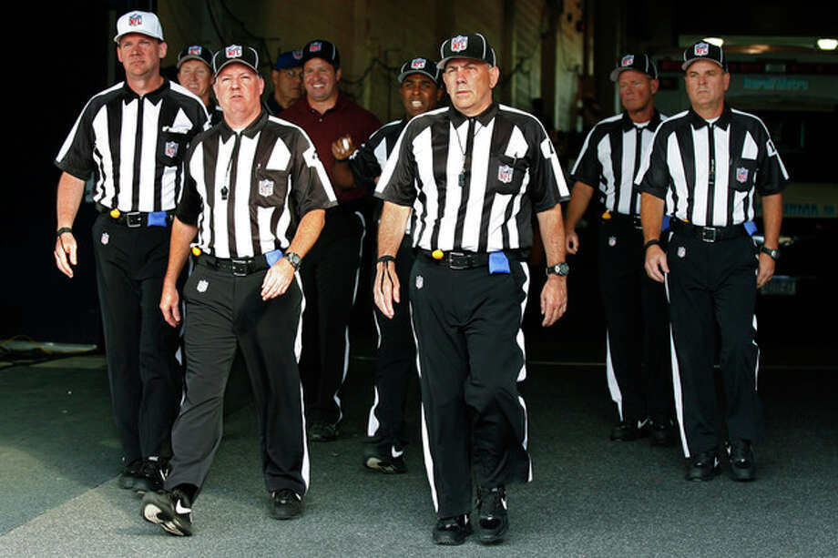 FILE - In this Aug. 9, 2012, file photo, officials walk towards the field for an NFL football game between the Buffalo Bills and the Washington Redskins in Orchard Park, N.Y. The NFL and referees' union reached a tentative agreement on Wednesday, Sept. 26, to end a three-month lockout that triggered a wave of frustration and anger over replacement officials and threatened to disrupt the rest of the season. (AP Photo/Bill Wippert, File) / FR170745 AP