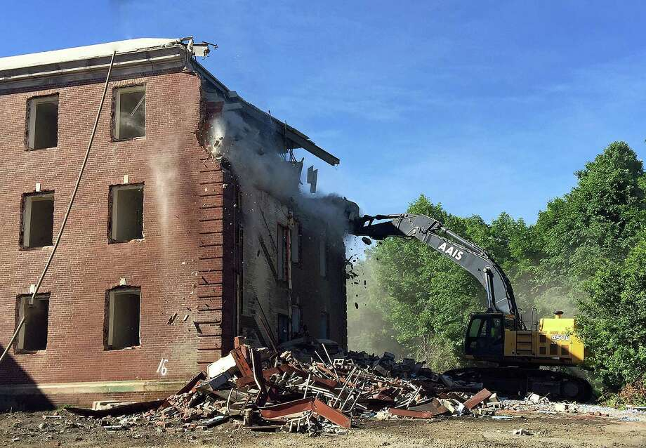 Demolition of a former Fairfield Hills Hospital administration building began Wednesday at Newtown's municipal campus. Photo: / Rob Ryser