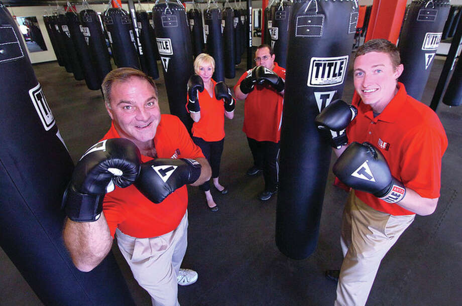 Hour Photo/ Alex von Kleydorff. L-R Tittle Gym Owner Eric van deBovenkamp, Assistant General Manager Lee Chase, General Manager Thomas Mordock, Dillon Burns, Corporate Trainer, in between some of the 54 hanging heavy bags. / 2012 The Hour Newspapers