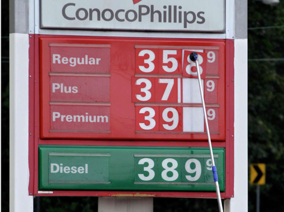 FILE-In this Monday, Sept. 24, 2012, file photo, a man changes fuel prices at a ConocoPhillips gas station in Little Rock, Ark. The price of oil fell to its lowest point in nearly two months Tuesday as persistent worries about the global economy overshadowed encouraging reports about U.S. consumer confidence and housing prices. (AP Photo/Danny Johnston) / AP