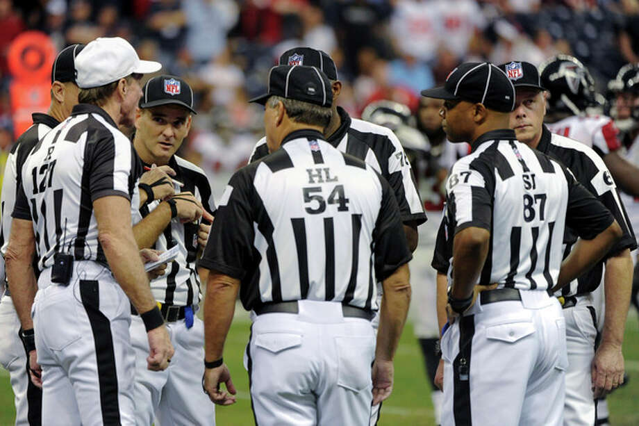 FILE - In this Dec. 4, 2011, file photo, officials confer in the fourth quarter of an NFL football game between the Atlanta Falcons and Houston Texans in Houston. The NFL and referees' union reached a tentative agreement on Wednesday, Sept. 26, 2012, to end a three-month lockout that triggered a wave of frustration and anger over replacement officials and threatened to disrupt the rest of the season. (AP Photo/Dave Einsel, File) / FR43584