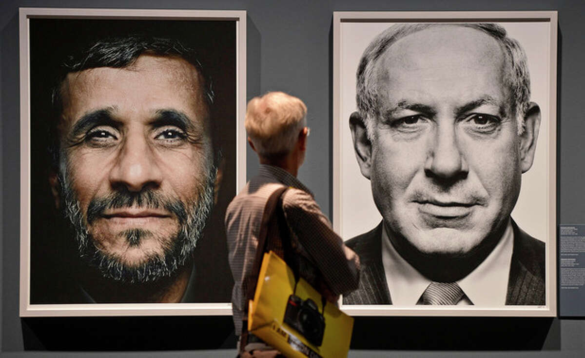 FILE - In this Wednesday, Sept. 19, 2012 file photo, a visitor looks at portraits of Iran's President Mahmoud Ahmadinejad and Israel's Prime Minister Benjamin Netanyahu during the exhibition