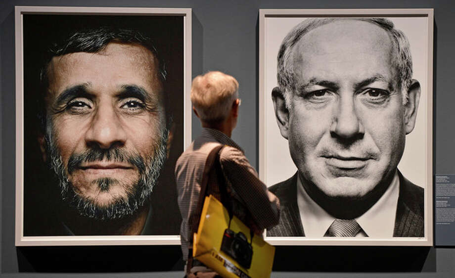 "FILE - In this Wednesday, Sept. 19, 2012 file photo, a visitor looks at portraits of Iran's President Mahmoud Ahmadinejad and Israel's Prime Minister Benjamin Netanyahu during the exhibition ""faces of power"" by Greek photo artist Platon Antoniou, shown at the Photokina 2012 in Cologne, Germany. Israeli Prime Minister Benjamin Netanyahu heads to the United Nations this week with a single item on his agenda: Iran. Netanyahu is convinced the Islamic Republic isn't taking American vows to block it from acquiring nuclear weapons seriously and that time is quickly running out to stop them. (AP Photo / Martin Meissner, File) / AP"