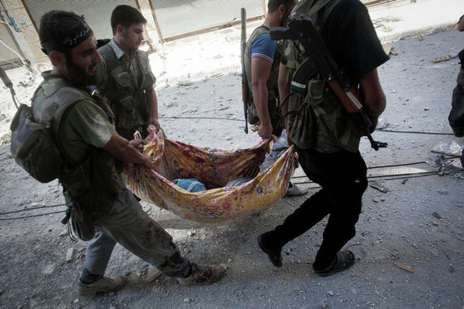 Free Syrian Army fighter carry the body of their comrade away from the front line during clashes against Syrian Army in Aleppo, Syria, Wednesday, Sept. 26, 2012. Syria's unrest began in March 2011 when protests calling for political change met a violent government crackdown. Many in the opposition have since taken up arms as the conflict morphed into a civil war that activists say has killed nearly 30,000 people. Over the past few months, the rebels have increasingly targeted security sites and symbols of regime power in a bid to turn the tide in the fighting.(AP Photo/Manu Brabo) / AP