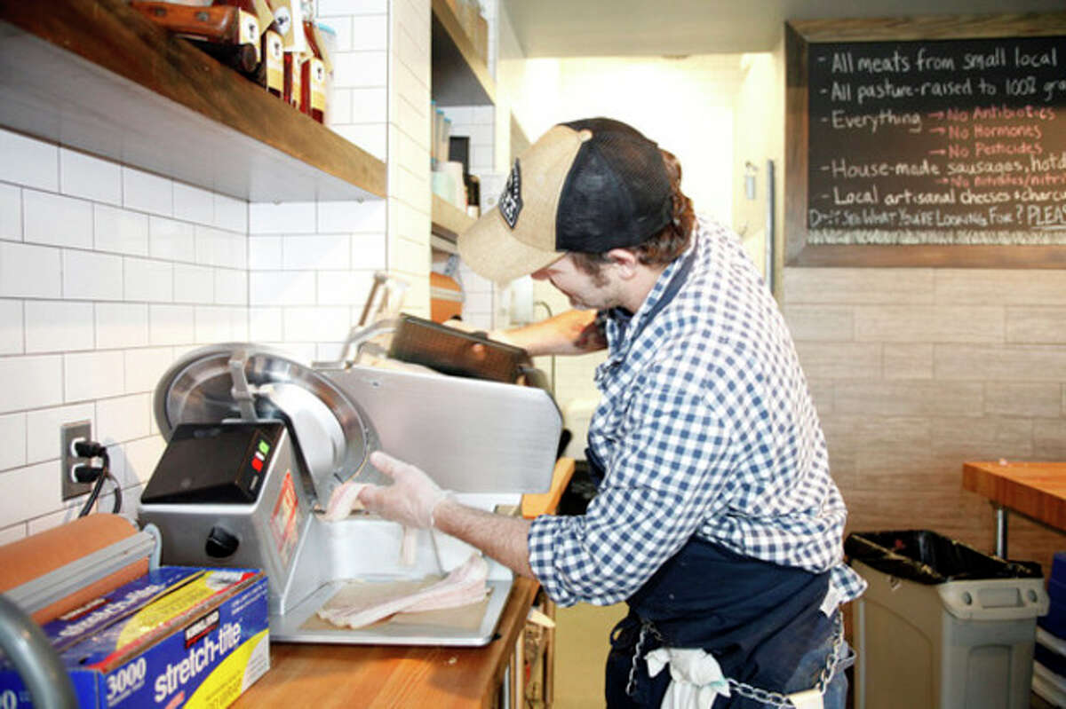 Hour photo / Danielle Robinson Butcher Mark Heppermann slices bacon at Craft Butchery in Westport Thursday afternoon.