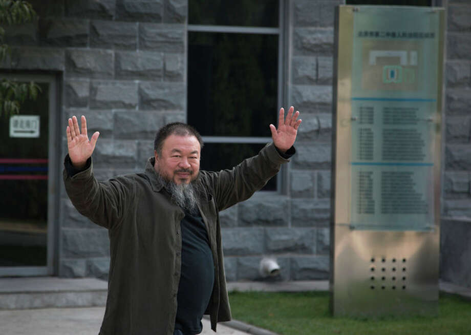 Chinese Activist artist Ai Weiwei waves to the journalists as he arrives to the Beijing No. 2 People's Intermediate Court in Beijing Thursday, Sept. 27, 2012. Chinese authorities on Thursday rejected Ai's second appeal of a $2.4 million tax fine, meaning his design company will have to pay the penalty. (AP Photo/Andy Wong) / AP