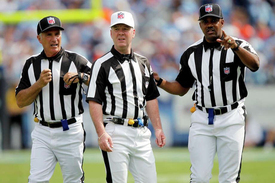 FILE - In this Sept. 25, 2011, file photo, officials confer in the third quarter of an NFL football game between the Denver Broncos and the Tennessee Titans in Nashville, Tenn. The NFL and referees' union reached a tentative agreement on Wednesday, Sept. 26, 2012, to end a three-month lockout that triggered a wave of frustration and anger over replacement officials and threatened to disrupt the rest of the season. (AP Photo/Wade Payne, File) / FR23601 AP