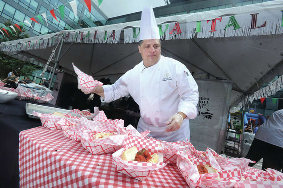 Chef Alfred Depole works the meatball and sausage and pepper tent Thursday for the Building and Land Technology's annual picninc with Little Italy as the theme. hour photo/Matthew Vinci
