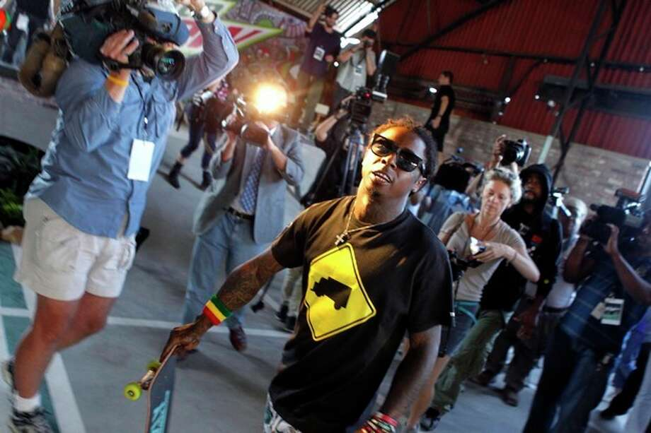 Recording artist Lil Wayne carries a skateboard at a new park he helped finance along with Glu Agency and Mountain Dew, in the Lower Ninth Ward of New Orleans, Wednesday, Sept. 26, 2012. (AP Photo/Gerald Herbert) / AP
