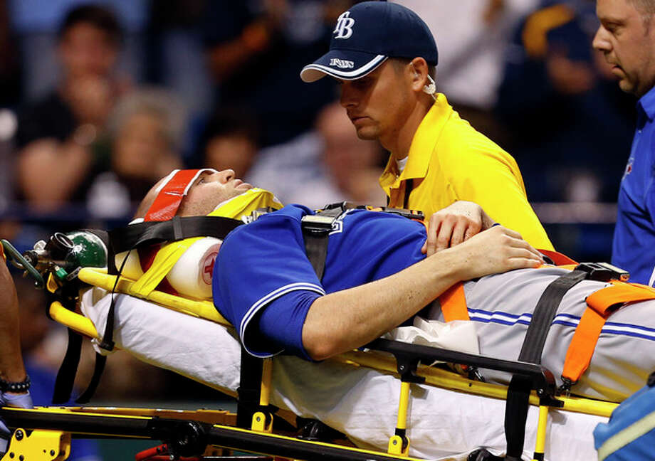 Toronto Blue Jays' J.A. Happ is attended to by medical personnel as he is taken off the field on a stretcher after being hit in the head by a line drive by Tampa Bay Rays' Desmond Jennings during the second inning of a baseball game Tuesday, May 7, 2013, in St. Petersburg, Fla. (AP Photo/Mike Carlson) / FR155492 AP