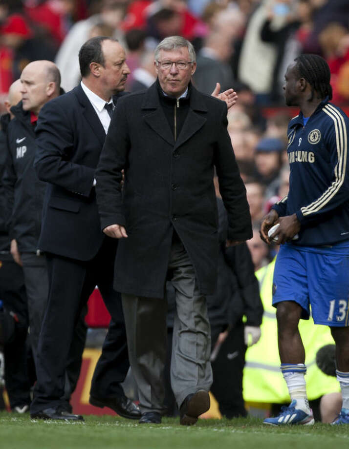Manchester United's manager Sir Alex Ferguson, centre, passes opposing manager Rafa Benitez, second left as he walks from the pitch after his team's 1-0 loss to Chelsea during their English Premier League soccer match at Old Trafford Stadium, Manchester, England, Sunday May 5, 2013. (AP Photo/Jon Super)