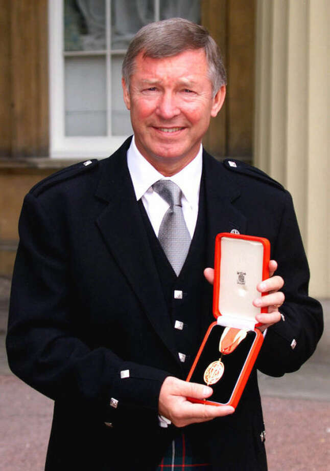 FILE - In this Tuesday, July 20, 1999 file photo Manchester United soccer manager Sir Alex Ferguson holds his knighthood insignia that was presented to him by Britain's Queen Elizabeth during an Investiture ceremony at Buckingham Palace, London. Manchester United said Wednesday May 8, 2013 that manager Alex Ferguson is retiring at the end of season. (AP Photo/John Stillwell, File)