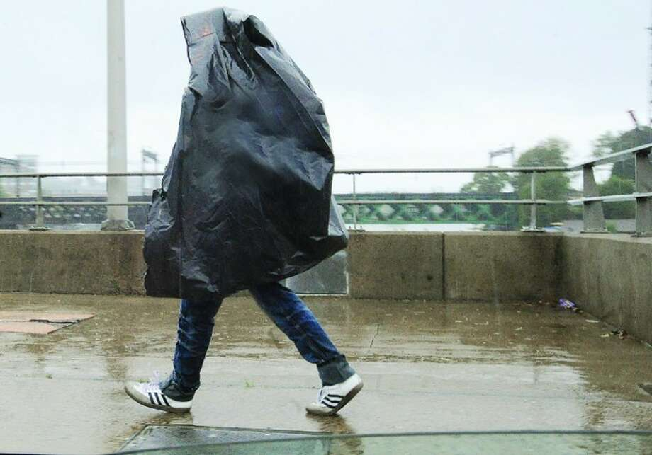 A pedstrian shields himeself with a plastic bag Friday morning as he crosses the Straffalino Bridge in Norwalk during the heavy rain. hour photo/Matthew Vinci