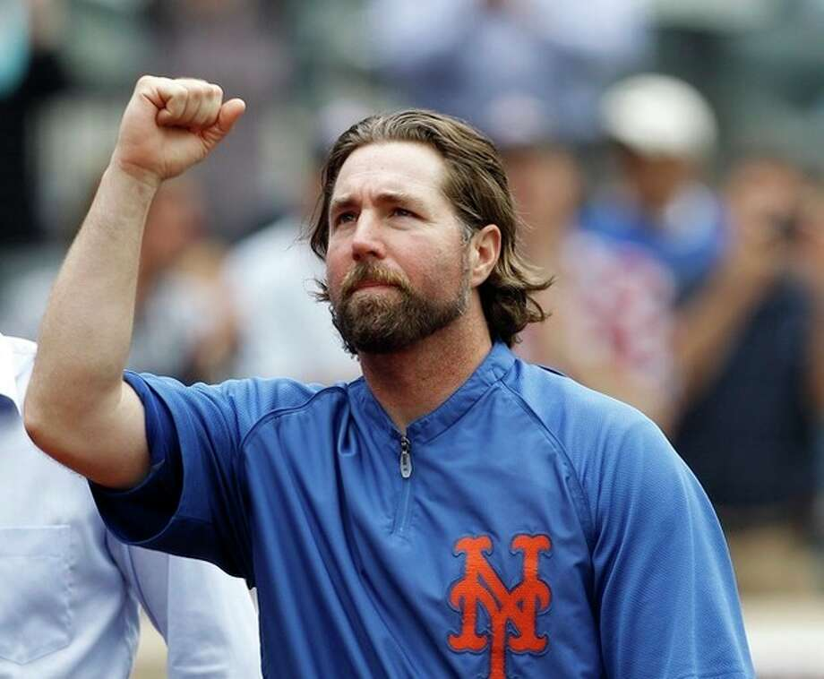 New York Mets starting pitcher R.A. Dickey acknowledges fans as he celebrates his 20th victory of the season after the Mets 6-5 win against the Pittsburgh Pirates in a baseball game at Citi Field in New York, Thursday, Sept. 27, 2012. (AP Photo/Kathy Willens) / AP