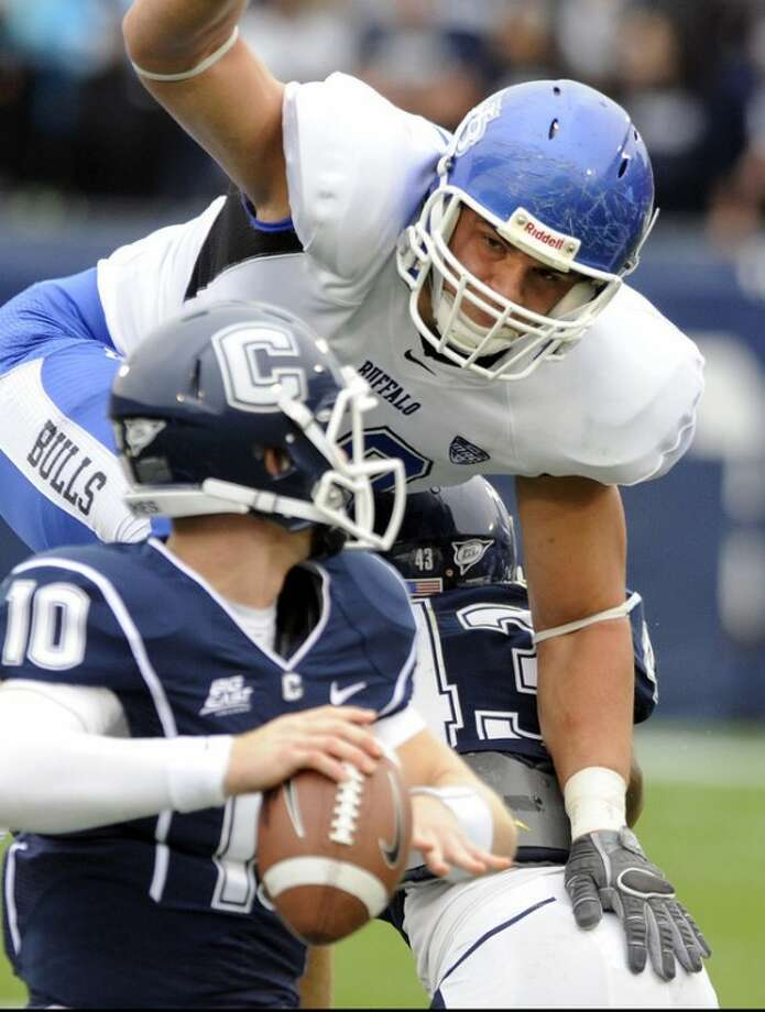 Connecticut's Chandler Whitmer, foreground, is pressured by Buffalo's Kristjan Sokolo during the first half of their NCAA college football game in East Hartford, Conn., on Saturday, Sept. 29, 2012. (AP Photo/Fred Beckham)