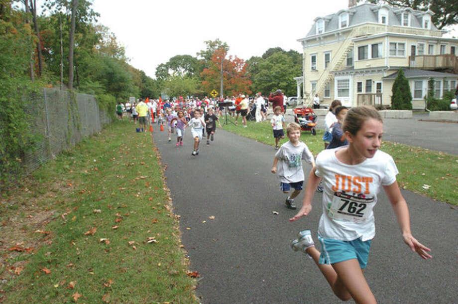 Kids head off the Run Between the Libraries Race off Belden Avenue Sunday, proceeds from the race go toward children's programming. hour photo/matthew vinci