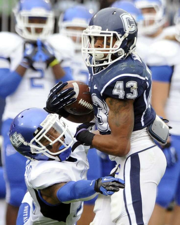 Connecticut's Lyle McCombs, right, eludes Buffalo's Najja Johnson during the first half of their NCAA college football game in East Hartford, Conn., on Saturday, Sept. 29, 2012. (AP Photo/Fred Beckham)
