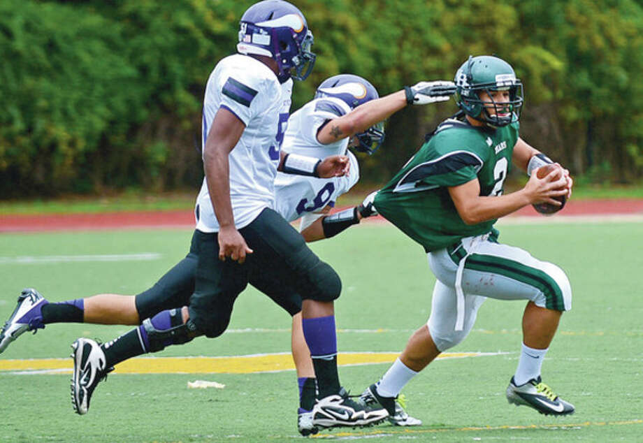 Hour photo/Erik TrautmannNorwalk quarterback Andy Lovo trieds to escape the grasp of a Westhill defender during Saturday's game in Stamford. The Vikings kept Lovo and the Bears bottled up on the way to a 13-0 victory. / (C)2012, The Hour Newspapers, all rights reserved