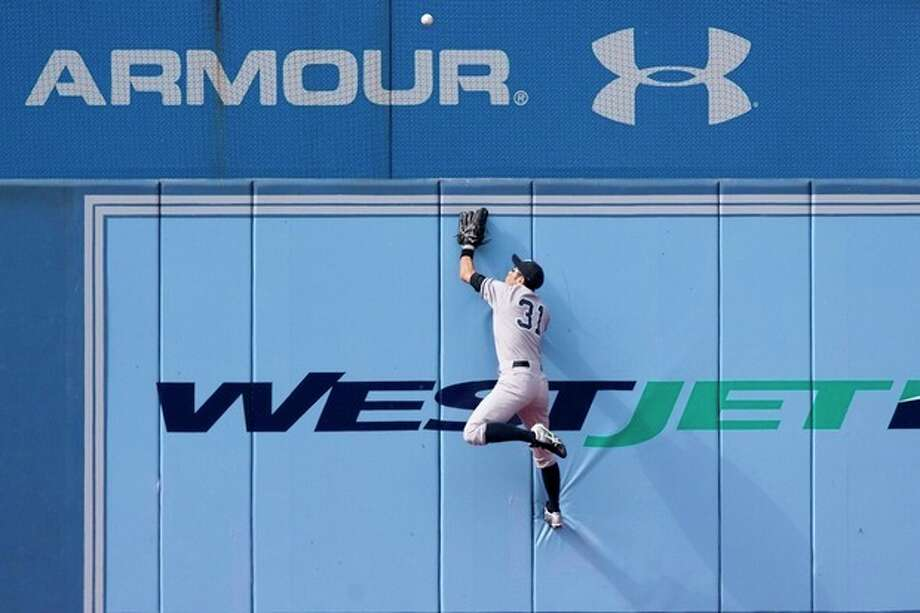New York Yankees' Ichiro Suzuki, of Japan, climbs the wall as he watches a homerun by Toronto Blue Jays' Rajai Davis' during the first inning of a baseball game in Toronto, Saturday, Sept. 29, 2012. (AP Photo/The Canadian Press, Chris Young) / CP