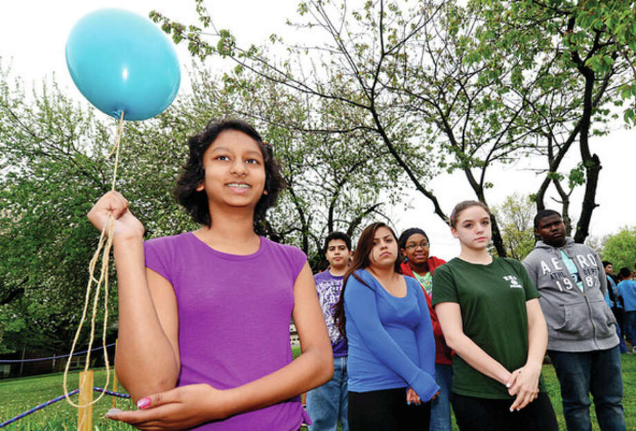 Hour photo / Erik TrautmannNathan Hale Middle School students including 8th grader Vrinda Kareddy prepare to release balloons and some wear teal to honor late computer teacher Eileen Hazard who died after a battle with ovarian cancer. / (C)2013, The Hour Newspapers, all rights reserved