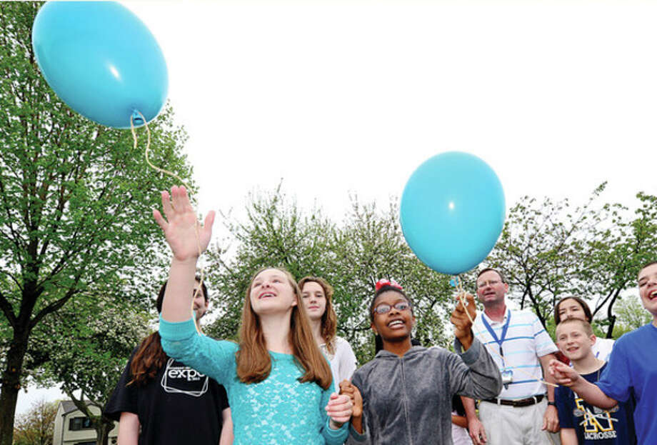 Hour photo / Erik TrautmannNathan Hale Middle School students including 6th graders Kaitlyn Belinsky and Angeline Moresca release balloons and some wear teal to honor late computer teacher Eileen Hazard who died after a battle with ovarian cancer during a brief ceremony Wednesday. / (C)2013, The Hour Newspapers, all rights reserved