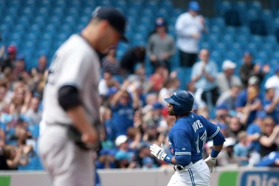 Toronto Blue Jays' Rajai Davis rounds the bases after hitting a home run off New York Yankees starting pitcher Andy Pettite, left, during the first inning of a baseball game in Toronto, Saturday, Sept. 29, 2012. (AP Photo/The Canadian Press, Chris Young) / CP
