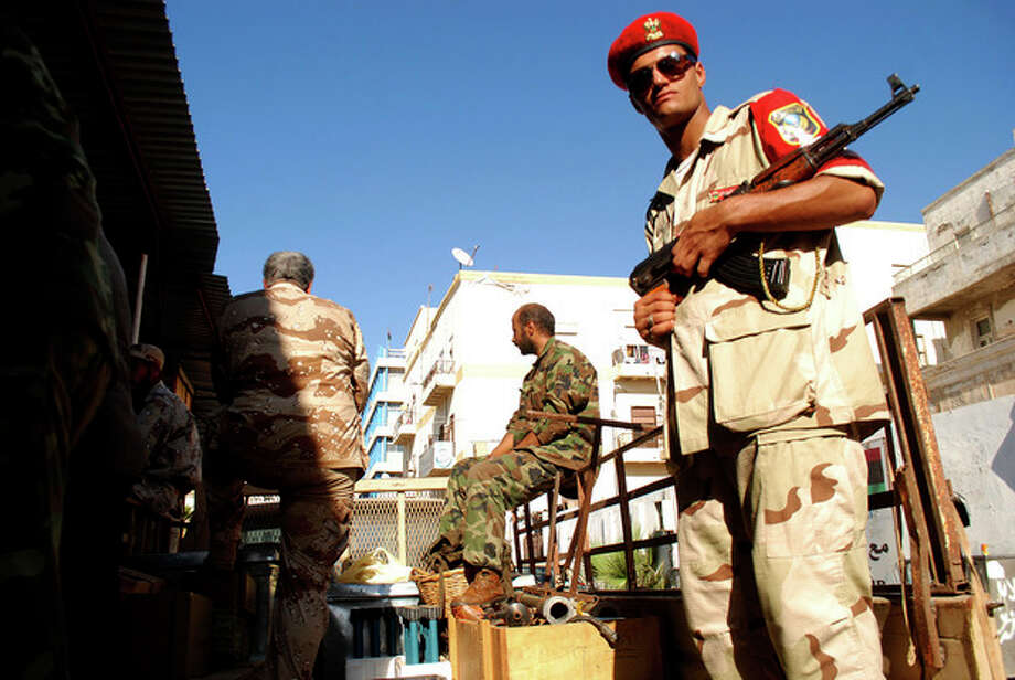 Libyan security forces stand guard as people turn in weapons in Benghazi, Libya, Saturday, Sept. 29, 2012. Hundreds of Libyans have converged on a main square in Benghazi in response to a call from the military to hand over their weapons, some driving in with armored personnel carriers, vehicles with mounted anti-aircraft guns and hundreds of rocket launchers. The call by the Libyan chiefs of staff was promoted on a private TV station earlier this month. But the call may have gained traction in the wake of the attack against the U.S. consulate in Benghazi in which the American ambassador and three staffers were killed. The attack was followed by a popular uproar against armed militias which have increasingly challenged government authorities. (AP Photo/Ibrahim Alaguri) / AP