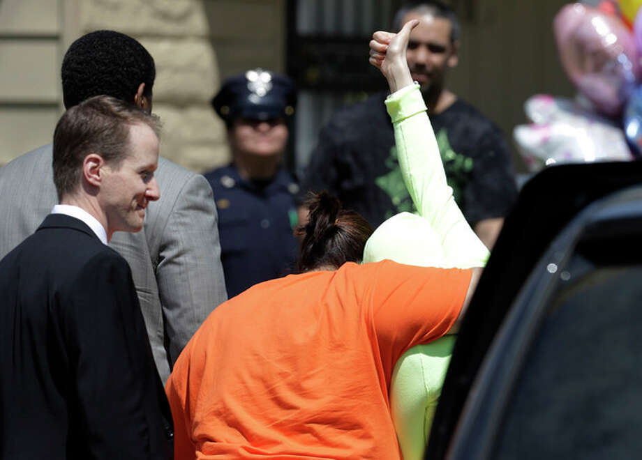 Gina DeJesus gives a thumbs-up as she is escorted toward her home Wednesday, May 8, 2013, in Cleveland. The three women held captive for about a decade at a run-down Cleveland house were apparently bound with ropes and chains, police said Wednesday, while charges were expected by the end of the day against the three brothers under arrest. (AP Photo/Tony Dejak) / AP