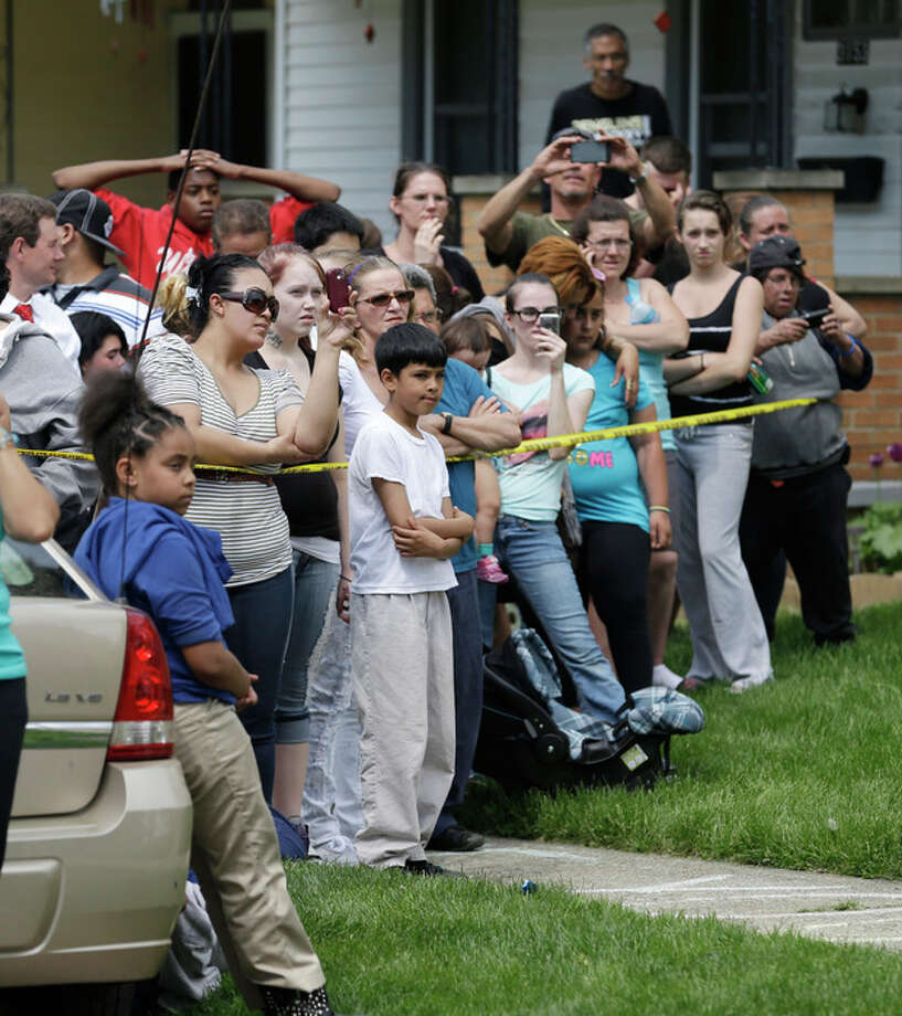 Neighborhood residents crowd the streets for the arrival of Gina DeJesus Wednesday, May 8, 2013, in Cleveland. DeJesus was one of three women held captive for about a decade at a run-down Cleveland house. Kidnapping and rape charges were filed Wednesday against the man arrested after the women missing were found alive at his home. (AP Photo/Tony Dejak) / AP