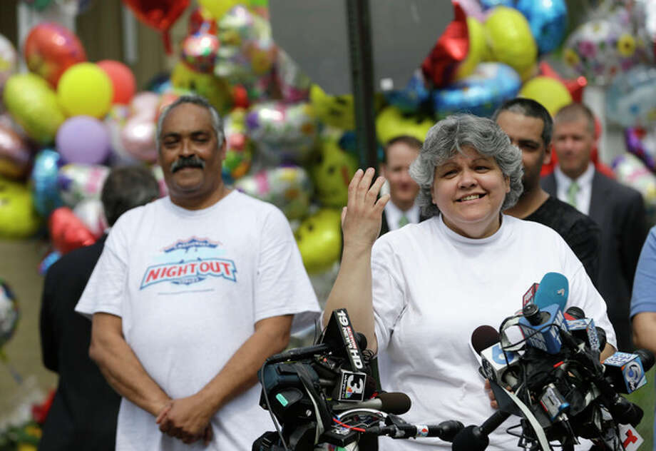 Sandra Ruiz, aunt of Gina DeJesus, speaks to the media after Gina's homecoming,Wednesday, May 8, 2013, in Cleveland. Felix, left, Gina's father smiles. The three women held captive for about a decade at a run-down Cleveland house were apparently bound with ropes and chains, police said Wednesday, while charges were expected by the end of the day against the three brothers under arrest. (AP Photo/Tony Dejak) / AP