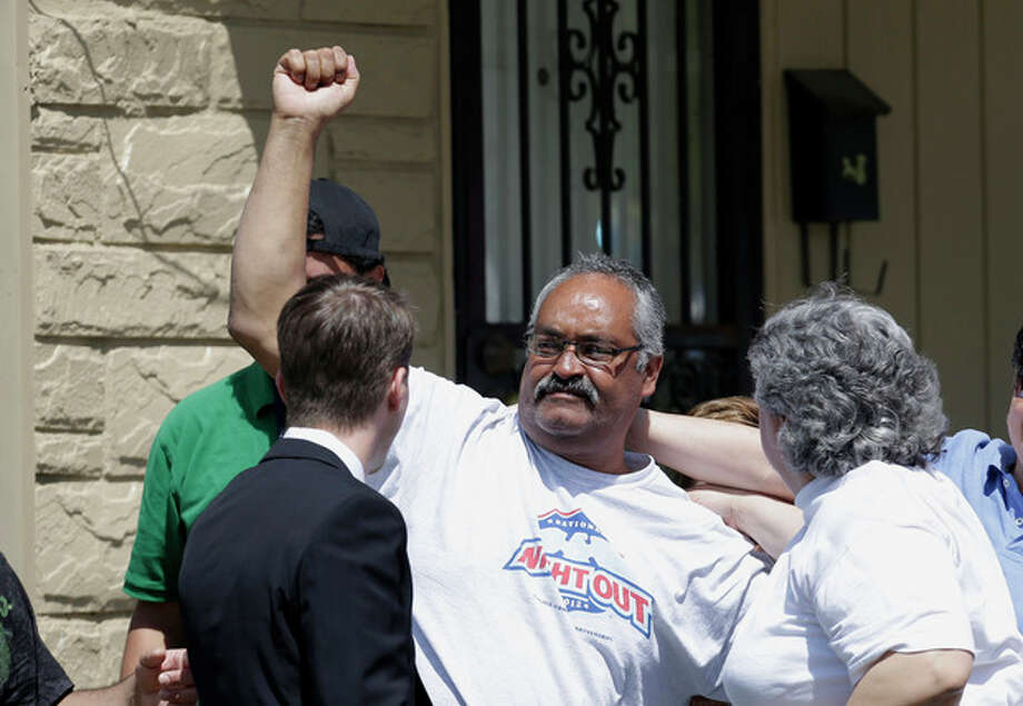 Felix DeJesus pumps his fist after bringing his daughter, Gina, home Wednesday, May 8, 2013, in Cleveland. The three women held captive for about a decade at a run-down Cleveland house were apparently bound with ropes and chains, police said Wednesday, while charges were expected by the end of the day against the three brothers under arrest. (AP Photo/Tony Dejak) / AP