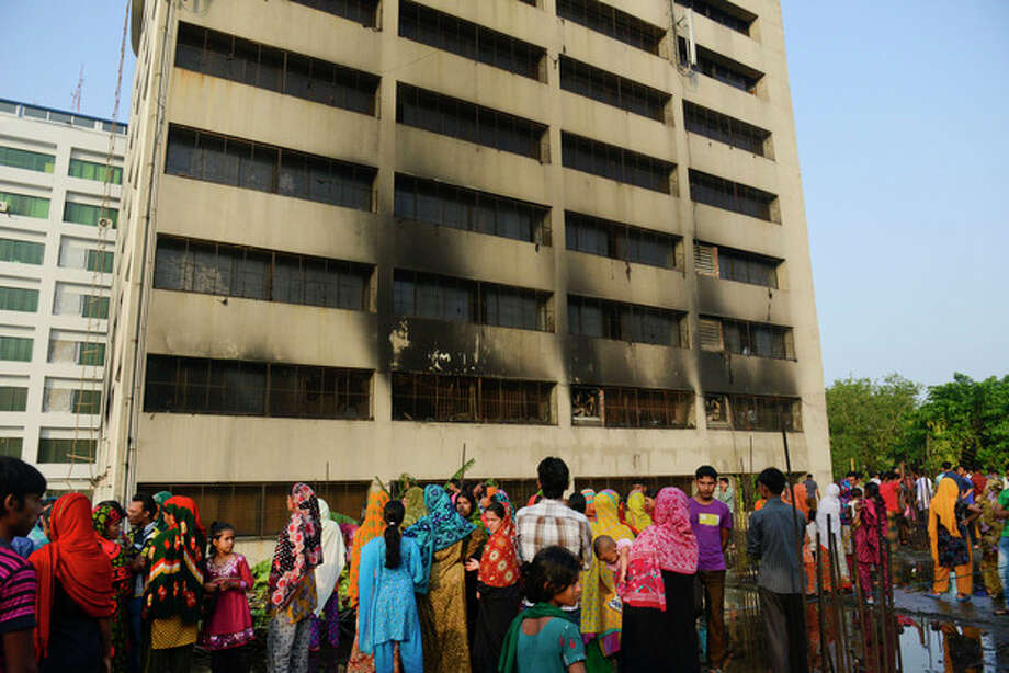 Workers stand outside an 11-story building that houses the Tung Hai Sweater Ltd. factory and apartments after a fire in Dhaka, Bangladesh, Thursday, May 9, 2013. The fire broke out in the building Wednesday night, not long after the up to 300 workers of the factory went home for the day, killing at least eight people officials said Thursday. (AP Photo/Ismail Ferdous) / AP