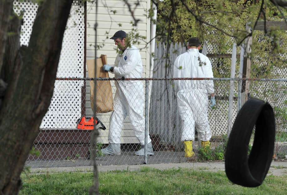 A member of the FBI evidence response team carries out a bag after searching a house near the home where three women were held Wednesday, May 8, 2013, in Cleveland. Amanda Berry, 27, Michelle Knight, 32, and Gina DeJesus, about 23, had apparently been held captive in the house nearby since their teens or early 20s, police said. (AP Photo/Roadell Hickman) / FR159470 AP