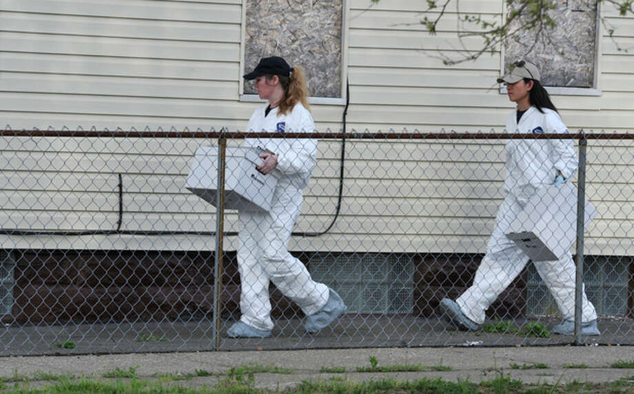 Members of the FBI evidence response team carries out a bag after searching a house near the home where three women were held Wednesday, May 8, 2013, in Cleveland. Amanda Berry, 27, Michelle Knight, 32, and Gina DeJesus, about 23, had apparently been held captive in the house nearby since their teens or early 20s, police said. (AP Photo/Roadell Hickman) / AP