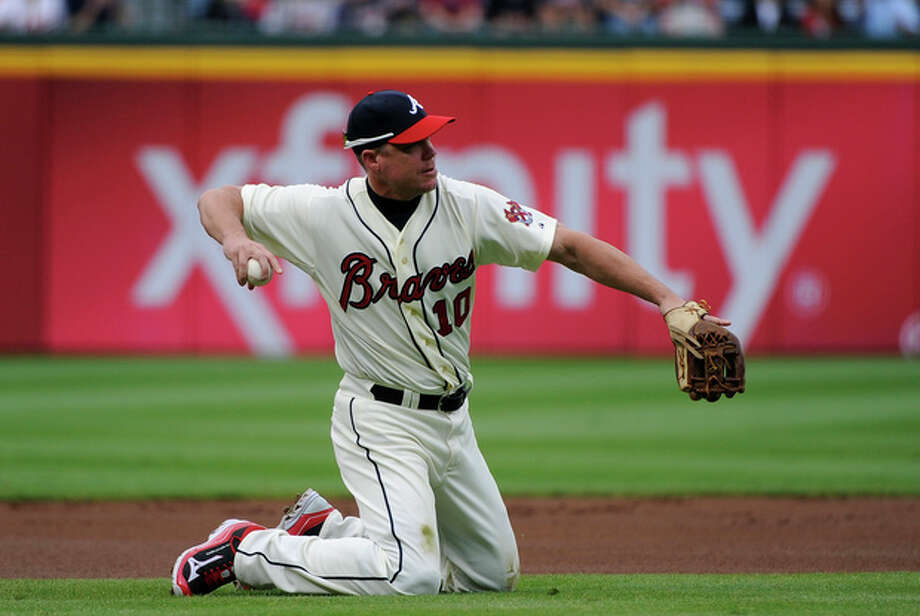 Atlanta Braves third baseman Chipper Jones fields a grounder by New York Mets' Ruben Tejada and throws to first base for the out during the first inning of their baseball game at Turner Field Sunday, Sept. 30, 2012, in Atlanta. (AP Photo/David Tulis) / FR170493 AP