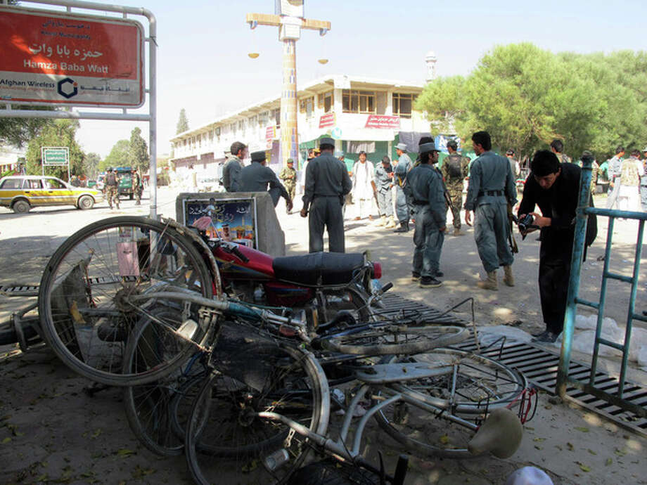 Afghan police secure the site of a suicide bombing in Khost, south of Kabul, Afghanistan, Monday, Oct. 1, 2012. The suicide bomber was driving a motorcycle packed with explosives and rammed it into a patrol of Afghan and international forces, killing over a dozen people, including three NATO service members and their translator, official said. (AP Photo/Nashanuddin Khan) / AP