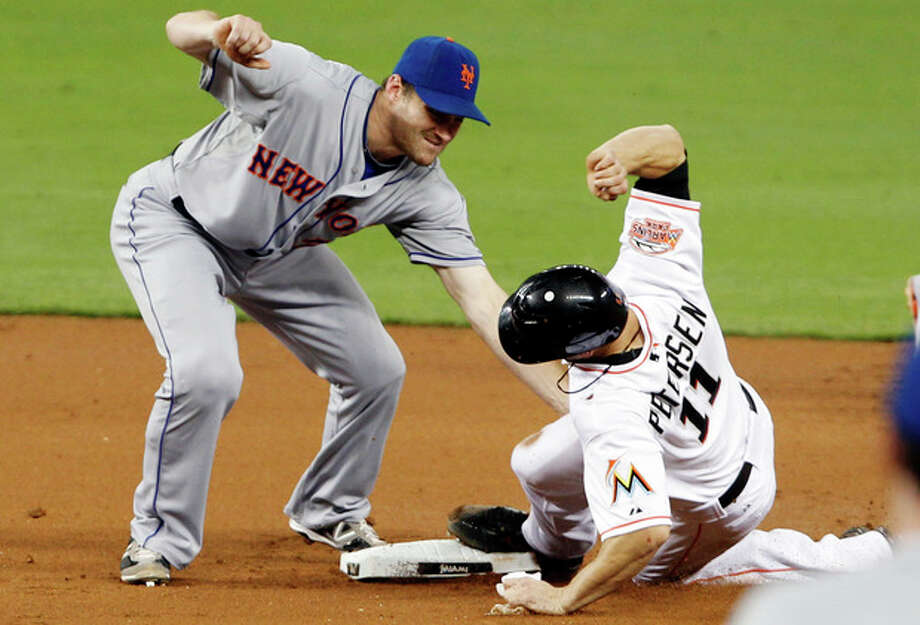 Miami Marlins' Bryan Petersen (11) is tagged out by New York Mets second baseman Daniel Murphy, left, after Petersen tried to steal second base in the first inning of a baseball game in Miami, Monday, Oct. 1, 2012. (AP Photo/Alan Diaz) / AP
